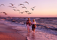 A senior couple walks on the beach at sunset.