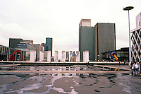 Paris: La Defense--looking east across asphalt, PARVIS or courtyard.. What is that marble Stonehenge ahead? Calder Stabile on left; Miro Sculpture on right. Photo '87.