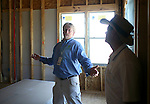 John Umphress, left, a conservation program specialist with Austin Energy, talks about features of a residential home that make it more energy efficient to Brian Domino, building superintendent for Standard Pacific Homes, on Monday, June 15, 2009 in Austin, Texas.  Double pane windows, therma ply heat resistant wall panels, and sealing duct work at outlets are examples of things contractors can do to meet Austin Energy's green building code...