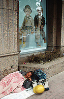China. Province of Zhejiang. Hangzhou. An homeless man sleeps on newspapers laid on the ground ( on the sidewalk) near a shop which sells children clothes. © 2004 Didier Ruef /