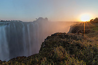 Sunrise over the Victoria Falls Gorge with colourful backlit spray.