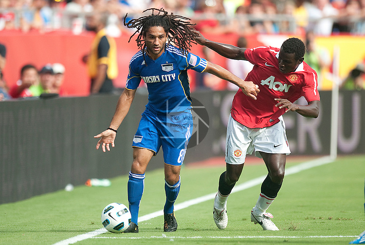 """July 25, 2010          Kansas City Wizards midfielder Stephane Auvray (8, left) tries to maintain control of the ball as he's pressured by Manchester United forward Mame Biram Diouf (32).  The Kansas City Wizards of Major League Soccer defeated Manchester United of the English Premier League 2-1 in an international friendly game on Sunday July 25, 2010 at Arrowhead Stadium in Kansas City, Missouri.  The game is the third of four stops for Manchester United on their """"Tour 2010""""."""