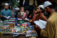 Bangladeshi Muslim devotees check religious books at a roadside shop in front of a mosque early morning in Dhaka, Bangladesh.