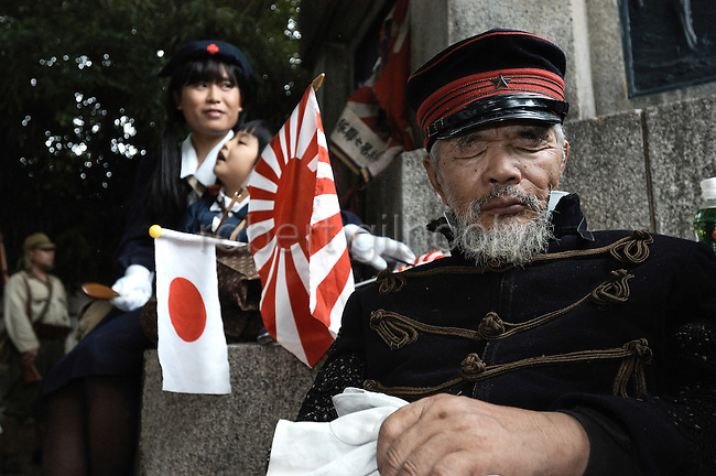 Japanese dressed in WWII era and Edo-period military attire take a rest in the grounds of Yasukuni Shrine in Tokyo, Japan. very year on August 15, the day Japan officially surrendered in WWII, tens of thousands of Japanese visit the controversial shrine to pay their respects to the 2.46 million war dead enshrined there, the majority of which are soldiers and others killed in WWII and including 14 Class A convicted war criminals, such as Japan's war-time prime minister Hideki Tojo. Each year speculation escalates as to whether the country's political leaders will visit the shrine, the last to do so being Junichiro Koizumi in 2005. Nationalism in Japan is reportedly on the rise, while sentiment against the nation by countries that suffered from Japan's wartime brutality, such as China, has been further aggravated by Japan's insistence on glossing over its wartime atrocities in school text books...Photographer:Robert Gilhooly..