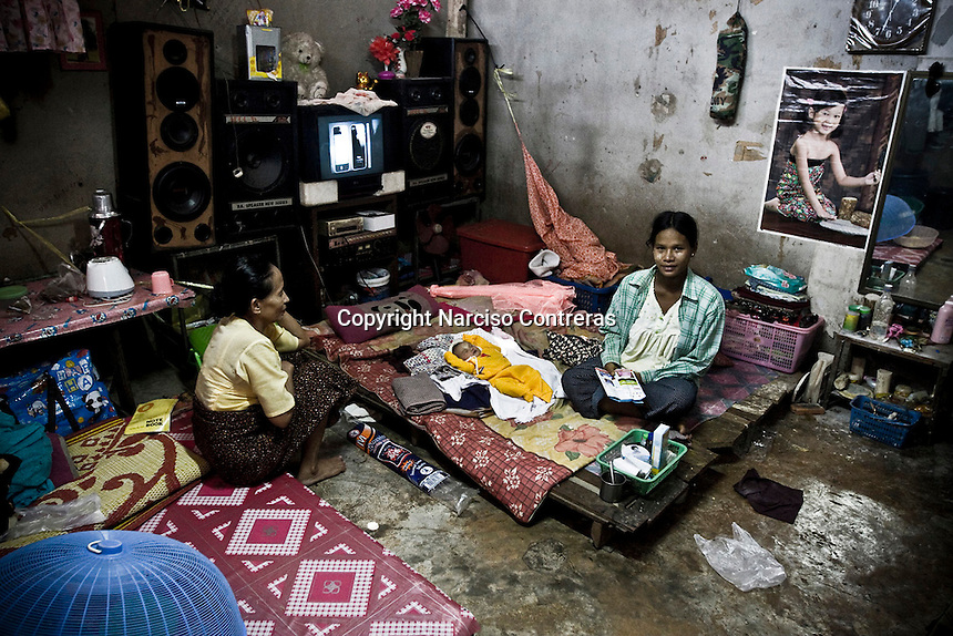 Burmses migrant family at burmese dwelling into the Thai factory. The migrant burmese workers live as property of the factory owner. The migrants suffer by human traffiking and persecution by thai authorities.