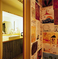A collection of children's drawings are displayed in the corner of a room. An open sliding door gives a view to a small bathroom beyond.