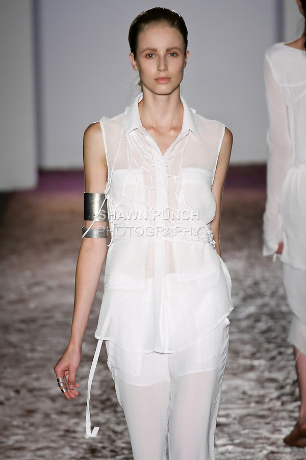 Model walks runway in a white ruru textured shirt, and white orak pant from the Kimberly Ovitz Spring 2013 runway show at Pier 57, during New York Fashion Week on September 6, 2012.
