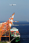 An All Nippon Airlines (ANA) Airlines plane flies over cranes used for loading cargo onto ships in Tokyo Bay, Tokyo, Japan.