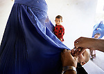 PESHAWAR, PAKISTAN, NOVEMBER 6, 2001 : Afghan women bring their children to the clinic in Nasir Bagh Refugee camp for polio immunization during the National Immunization Days in Pakistan. Pakistan is one of the six remaining Polio endemic countries, where the populations at risk is unable to get basic health services because of isolation, neglect, civil strife or war. In 2005, pakistan had 25 confirmed polio cases (Photo by Jean-Marc Giboux)