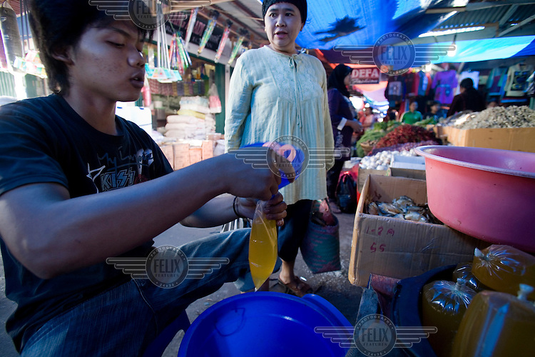 A vendor pours palm oil to be used for cooking into plastic bags, for sale in a market in Rengat.