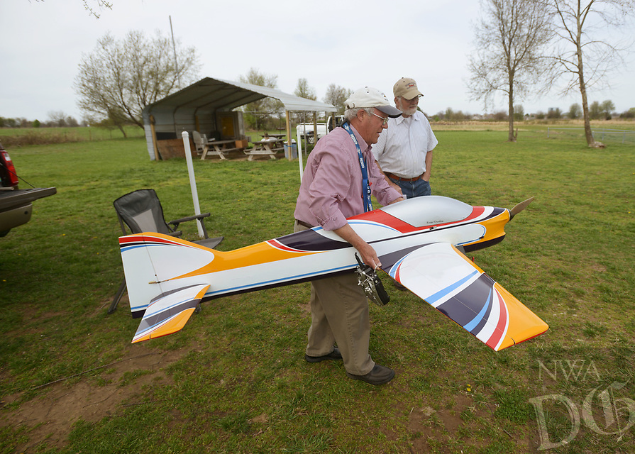 NWA Democrat-Gazette/BEN GOFF @NWABENGOFF<br /> Russell Rhodes of Rogers carries his radio control '2 meter pattern plane' to the flight line with help from Bill Parker of Bentonville Sunday, March 26, 2017, while flying at the Benton County Flying Tigers arifield in Rogers. The Benton County Flying Tigers, an Academy of Model Aeronautics (AMA) sanctioned radio control club, meet on the first Tuesday of each month except in December and January. Members can be seen flying at the grass airfield most weekends when weather permits.