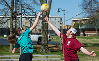 Callie Neumann of Bentonville and Jake Smith of St. Louis go for the ball Wednesday, March 25, 2020, while playing volleyball at Memorial Park in Bentonville. Bentonville Parks and Recreation staff removed nets from the sand volleyball courts Tuesday and from the adjacent tennis courts Wednesday. The group found a rope nearby that they strung between the posts to act as a net, but their game was cut short when a Bentonville police officer asked them to leave. Parks and recreation staff added more signage making clear that the park was closed. All Bentonville city parks have been closed, except for the trails, to combat the spread of the covid-19 pandemic.    <br /> Go to nwaonline.com/photos to see more photos.<br /> (NWA Democrat-Gazette/Ben Goff)
