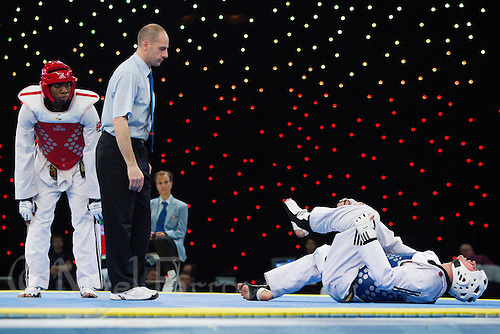 04 MAY 2012 - MANCHESTER, GBR - Lutalo Muhammad (GBR) of Great Britain looks on as his opponent in the men's -87kg category semi final, Ali Sari (TUR) of Turkey (right), lies on the mat holding his leg during the 2012 European Taekwondo Championships at Sportcity in Manchester, Great Britain (PHOTO (C) 2012 NIGEL FARROW)