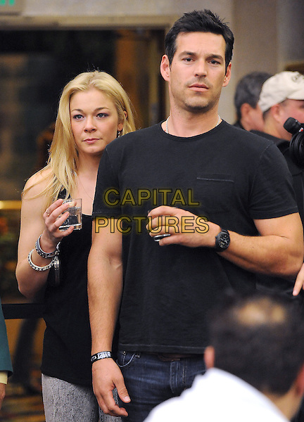 LeANN RIMES & EDDIE CIBRIAN.The World Poker Tour Celebrity Invitational Tournament held at The Commerce Casino in The City of Commerce, California, USA..February 20th, 2010              .half length black top drink beverage couple t-shirt   .CAP/RKE/DVS.©DVS/RockinExposures/Capital Pictures.