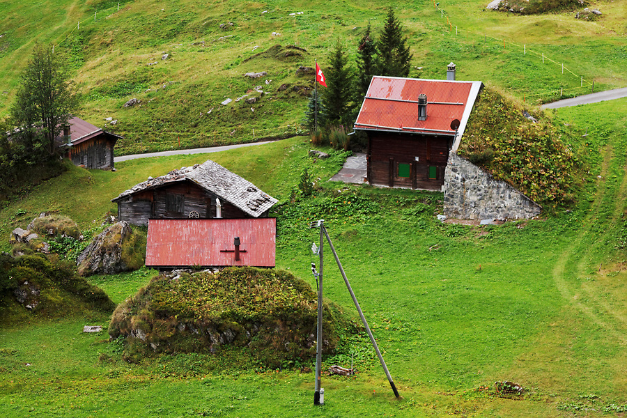 Buildings protected from avalanche by stone barriers in the Swiss mountain village of Schiltalp, Bernese Oberland, Switzerland