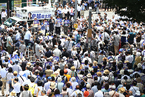 People watch and listen as Shuntaro Torigoe, Japanese journalist and a joint candidate of opposition parties attends a stump speech during his campaign in front of Shinjuku Station, Tokyo, Japan on July 14, 2016. Official election campaign was kicked off on Thursday for the July 31 Tokyo gubernatorial election. (Photo by Shingo Ito/AFLO)