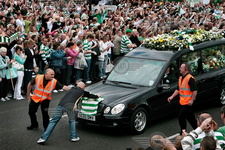 Thousands of people stand outside Celtic Park to pay their respects to the late Tommy Burns, player, manager and coach at Celtic Football Club in Glasgow. He died from cancer aged 51. A fan runs in front of the funeral car which is carrying his body to lay a Celtic jersey on the bonnet.