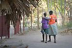 """Two students walk together at the Loreto Girls Secondary School in Rumbek, South Sudan. The school is run by the Institute for the Blessed Virgin Mary--the Loreto Sisters--of Ireland. <br /> <br /> The school implements an extended family system where first year students are considered the """"daughters"""" of second year students, who are considered """"mothers."""" Third year students are """"grandmothers,""""  and fourth year students are """"great grandmothers."""" Initiation into the school and a lot of discipline are handled through this """"family""""  system."""