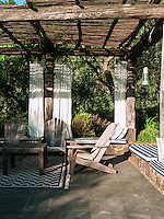 Adirondack chairs in the pergola in the secluded garden.