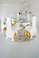 The dining area in the Villa Siam at Iniala designed by Eggarat Wongcharit features a set of futuristic looking chairs grouped around a glass-topped table