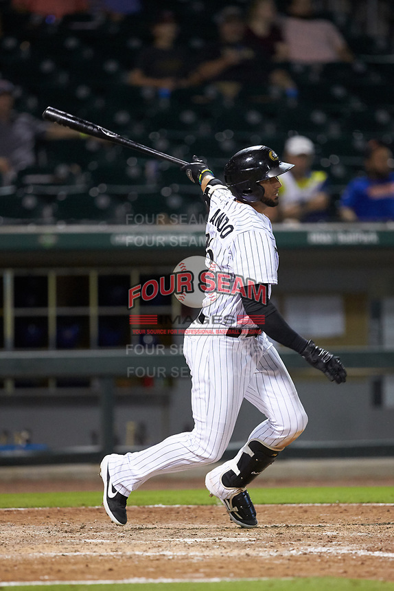 Paulo Orlando (16) of the Charlotte Knights follows through on his swing against the Durham Bulls at BB&T BallPark on July 31, 2019 in Charlotte, North Carolina. The Knights defeated the Bulls 9-6. (Brian Westerholt/Four Seam Images)