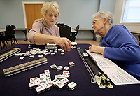 NWA Democrat-Gazette/DAVID GOTTSCHALK Alice Boepple (right) leans in to instruct Brenda Crum on the use of her tiles Monday, March 12, 2018, during a Mah Jongg lesson at the Rogers Adult Wellness Center. Organized games of Mah Jongg are played weekly on Mondays and Wednesdays. Lessons are available before play on Mondays. Mah Jongg is a tile-based game that was developed in China.