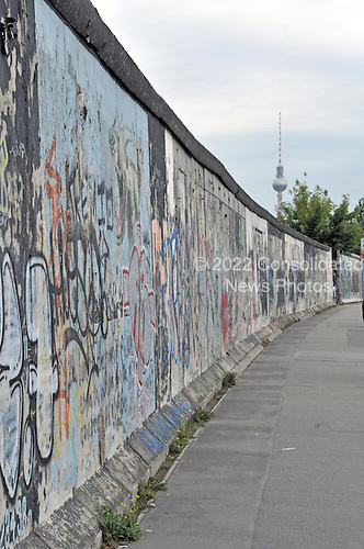 "Berlin, Germany - August 11, 2009 -- Portion of the longest remaining section of the Berlin Wall showing the graffiti on its eastern side in Berlin, Germany on Tuesday, August 11, 2009.  This remaining part of the wall is known as the ""East Side Gallery"" in Friedrichshain near the Oberbaumbrücke over the Spree River.  The Fernsehturm (German for ""television tower"") can be seen on the right side of the image..Credit: Ron Sachs / CNP"