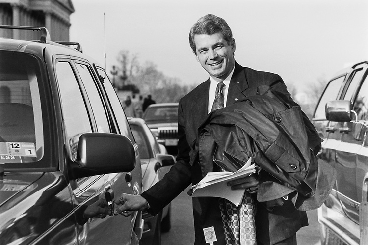 Rep. Dave McCurdy, D-Okla. gladly departs from the Capitol Hill with luggage and coat. Hashly puts key on his car door on Dec. 2, 1991. (Photo by Laura Patterson/CQ Roll Call)