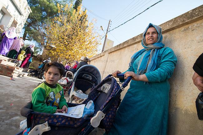 Verteilstelle des Kurdischen Roten Halbmond &quot;Heyva Sor A Kurd in Amude.<br /> Beduerftige koennen sich dort kostenfrei Medikamente, Babynahrung und Windeln abholen.<br /> Im Bild: Frauen an diesem Tag an um Babynahrung und Windeln zu bekommen.<br /> 17.12.2014, Amude/Rojava/Syrien<br /> Copyright: Christian-Ditsch.de<br /> [Inhaltsveraendernde Manipulation des Fotos nur nach ausdruecklicher Genehmigung des Fotografen. Vereinbarungen ueber Abtretung von Persoenlichkeitsrechten/Model Release der abgebildeten Person/Personen liegen nicht vor. NO MODEL RELEASE! Nur fuer Redaktionelle Zwecke. Don't publish without copyright Christian-Ditsch.de, Veroeffentlichung nur mit Fotografennennung, sowie gegen Honorar, MwSt. und Beleg. Konto: I N G - D i B a, IBAN DE58500105175400192269, BIC INGDDEFFXXX, Kontakt: post@christian-ditsch.de<br /> Bei der Bearbeitung der Dateiinformationen darf die Urheberkennzeichnung in den EXIF- und  IPTC-Daten nicht entfernt werden, diese sind in digitalen Medien nach &sect;95c UrhG rechtlich geschuetzt. Der Urhebervermerk wird gemaess &sect;13 UrhG verlangt.]