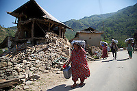Nepalese people carry UK aid shelter kits back to the remains of their homes, 10 days after the 7.8 magnitude earthquake struck the country on 25 April 2015. The UK is sending thousands of shelter kits and other essential aid in response to the disaster.<br /> <br /> Picture: Russell Watkins/DFID
