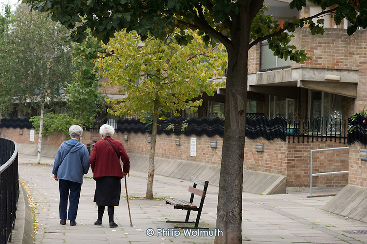 Two elderly women walk along the towpath of the Grand Union Canal in Paddington, London.