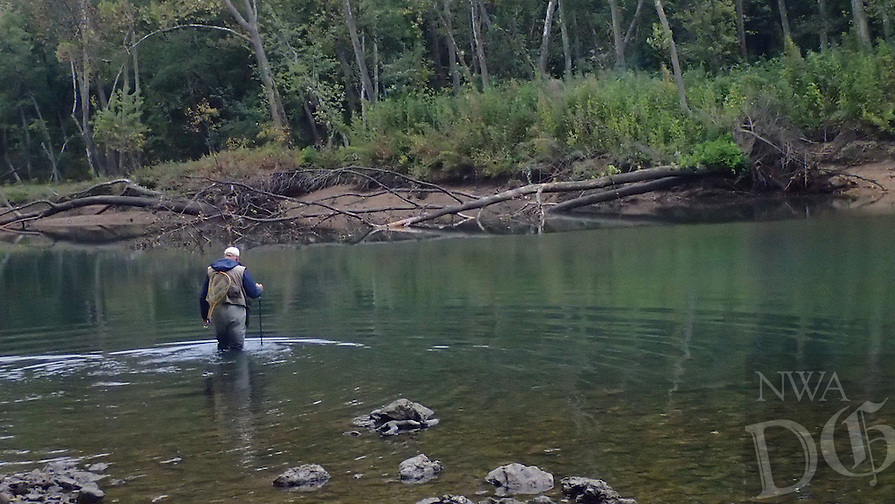 NWA Democrat-Gazette/FLIP PUTTHOFF <br /> Gary Henderson wades Oct. 13 2016 to his third fishing spot of the morning. It turned out to be his best area, where he caught several trout on micro jigs.