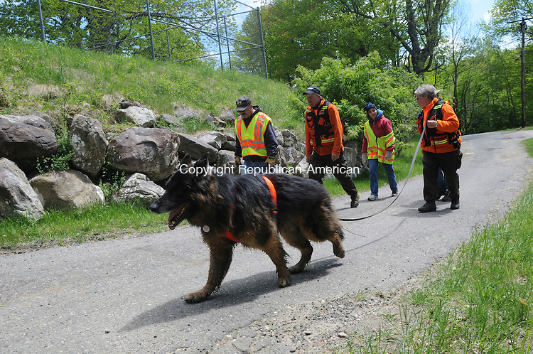 WINCHESTER, CT-09 MAY 2010-050910IP01- (l to r) Timber the dog leads Dave Battista of the Winchester Fire Department, J.R. Unitas of Madison, Pam Stenman of Winchester, and Tricia Heldmann of Colchester on a search during a training exercise at Greenwood Trails Camp in Winchester on Sunday. The Winchester Volunteer Fire Department and TASK-9, a trailing and air scent tracking organization, held a joint training excercise in which dogs searched for a &quot;missing&quot; person using scent. TASK-9 is a not-for-profit group that works with emergency responders throughout Southern New England to find lost or missing people.<br /> Irena Pastorello Republican-American