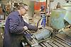 Man operating metal working machine at engineering works,