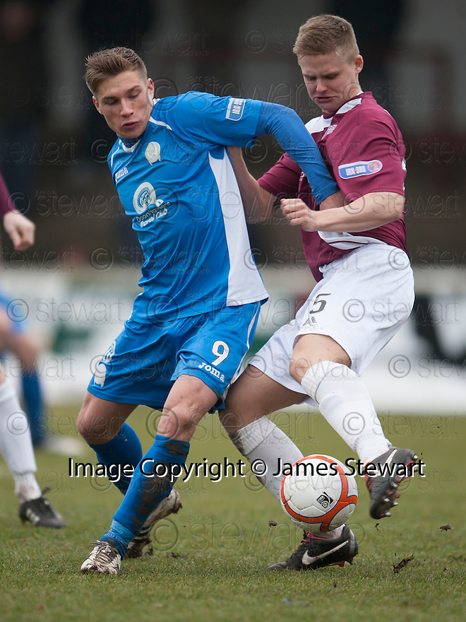 Queen of the South's Gavin Reilly and Arbroath's Michael Travis challenge for the ball.