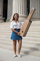 A young woman poses with her home-made eclipse viewers on the steps outside of MIT's Building 7 on Massachusetts Avenue on the campus of MIT after a solar eclipse viewing event in Cambridge, Massachusetts, USA, on Mon., Aug. 21, 2017. This solar eclipse is the first in nearly 40 years to have a path observable total eclipse from coast to coast in the United States. People at this location in Massachusetts, however, only observed about 66% coverage of the moon over the sun.