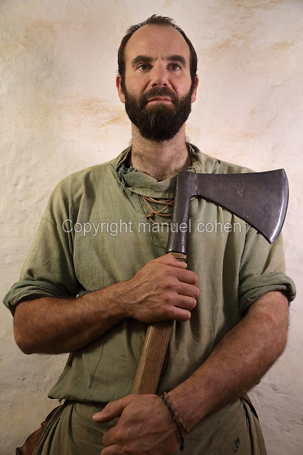 Nicolas Touchefeu, carpenter on the Guedelon project since 15/03/2004, wearing medieval costume and holding an axe, at the Chateau de Guedelon, a castle built since 1997 using only medieval materials and processes, in Treigny, Yonne, Burgundy, France. The Guedelon project was begun in 1997 by Michel Guyot, owner of the nearby Chateau de Saint-Fargeau, with architect Jacques Moulin. It is an educational and scientific project with the aim of understanding medieval building techniques and the chateau should be completed in the 2020s. Picture by Manuel Cohen