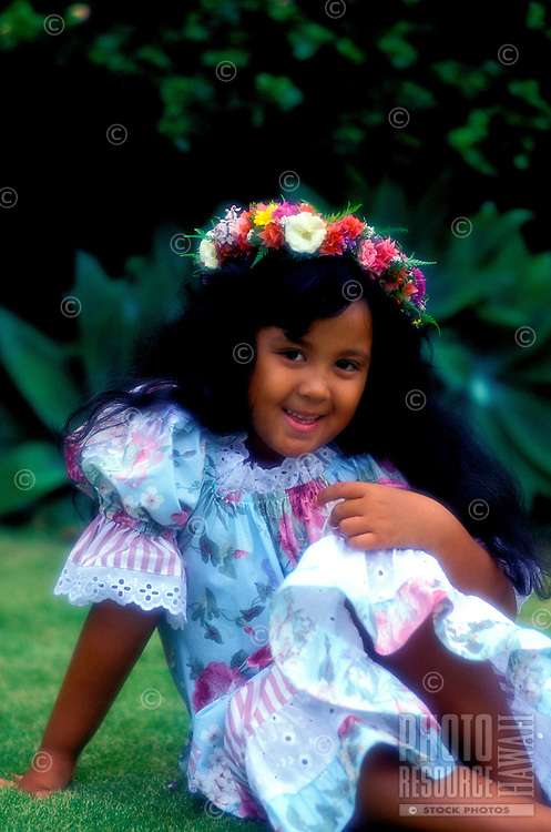 A beautiful smiling young Hawaiian girl dressed in a muu muu and wearing a haku lei (floral headpiece) sits on the grass in front of green foliage.