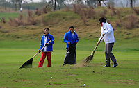 Green staff sweep the practice range during Sunday's Final Round of the 2014 BMW Masters held at Lake Malaren, Shanghai, China. 2nd November 2014.<br /> Picture: Eoin Clarke www.golffile.ie