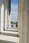 Bright sunlight illuminates the Vermont granite stone of the Lincoln Monument on a spring day. Several visitors sit facing the Washington Monument and the reflecting pool on a spring day in Washington D.C.. The World War 2 Monument and the Capital building can be seen in the backround.
