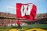 Wisconsin Badgers cheerleader runs with the Motion W flag after a touchdown during an NCAA College Big Ten Conference football game against the Minnesota Golden Gophers Saturday, November 25, 2017, in Minneapolis, Minnesota. The Badgers won 31-0. (Photo by David Stluka)