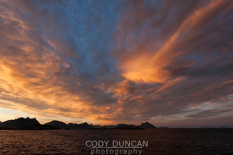 Colorful sunset fills sky over mountains, Stamsund, Vestvågøy, Lofoten Islands, Norway