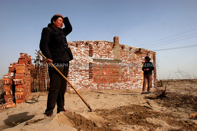 3/27/2004--Aksu, Xinjiang Province, China..Mu Guixiang (38, left) shovels sand outside her home on the outskirts of Atsu, on the northern edge of China's Taklimakan Desert. The Taklimakan, the world's second largest desert, is located in northwest China, and the Chinese government is working on one of the largest tree planting projects ever to prevent the desert from expanding. The area is also home to recent Han Chinese immigrants to the region, many who have come to farm on land reclaimed from the desert...Photograph by Stuart Isett .©2004 Stuart Isett. All rights reserved
