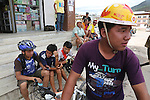 Mountain bike enthusiasts with home-made Nike helmet. Punakha town centre with a mix of traditional and modern lifestyles, Bhutan..Bhutan the country that prides itself on the development of 'Gross National Happiness' rather than GNP. This attitude pervades education, government, proclamations by royalty and politicians alike, and in the daily life of Bhutanese people. Strong adherence and respect for a royal family and Buddhism, mean the people generally follow what they are told and taught. There are of course contradictions between the modern and tradional world more often seen in urban rather than rural contexts. Phallic images of huge penises adorn the traditional homes, surrounded by animal spirits; Gross National Penis. Slow development, and fending off the modern world, television only introduced ten years ago, the lack of intrusive tourism, as tourists need to pay a daily minimum entry of $250, ecotourism for the rich, leaves a relatively unworldly populace, but with very high literacy, good health service and payments to peasants to not kill wild animals, or misuse forest, enables sustainable development and protects the country's natural heritage. Whilst various hydro-electric schemes, cash crops including apples, pull in import revenue, and Bhutan is helped with aid from the international community. Its population is only a meagre 700,000. Indian and Nepalese workers carry out the menial road and construction work.