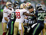 Umpire Rich Hall, center, breaks up a scuffle between the Seattle Seahawks and the  San Francisco 49ers  at CenturyLink Field in Seattle, Washington on December 14, 2014.  The Seahawks beat the 49ers 17-7.    © 2014. Jim Bryant Photo. All Rights Reserved.