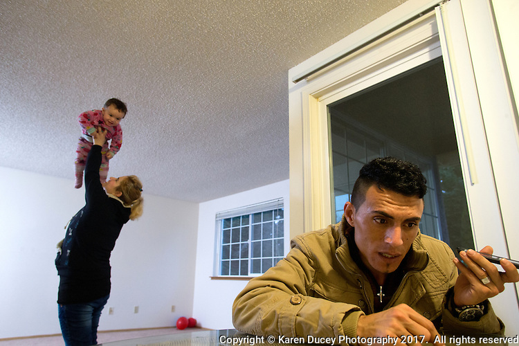 Shatha Sulaiman Kheder, 27, (left) plays with her son Steven Adil Kheder, 10 months, while her husband Adil Kheder Nimr, 27, (right) speaks with a reporter about their family still in Iraq from their new apartment in Tukwila, Wash. on January 30, 2017. The family arrived in the United States as refugees from Iraq on January 19, 2017, the day after Donald Trump was sworn in as the 45th president of the United States. They are concerned about thirteen of their family members still in Iraq. Trump signed an executive order last Friday restricting immigration from seven Muslim countries, suspending all refugee admission for 120 days, and bans all Syrian refugees indefinitely.  (Photo by Karen Ducey)