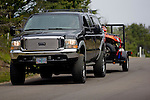 Black Ford pickup towing ATV