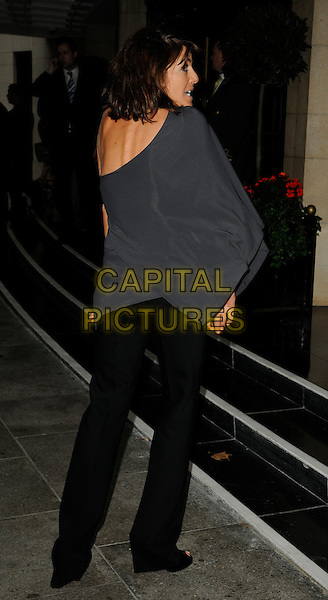 CLAUDIA WINKLEMAN.The Harper's Bazaar Women of the Year Awards, Dorchester hotel, London, England..September 7th, 2009.full length black trousers grey gray off the shoulder top on sleeve back behind rear profile skinny spine .CAP/CAN.©Can Nguyen/Capital Pictures.
