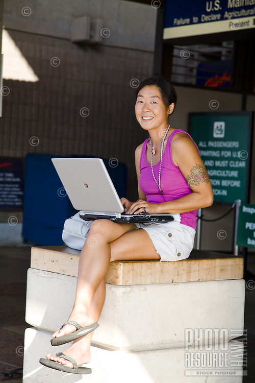 Attractive Asian- American woman working on her laptop computer at Kahului Airport on Maui