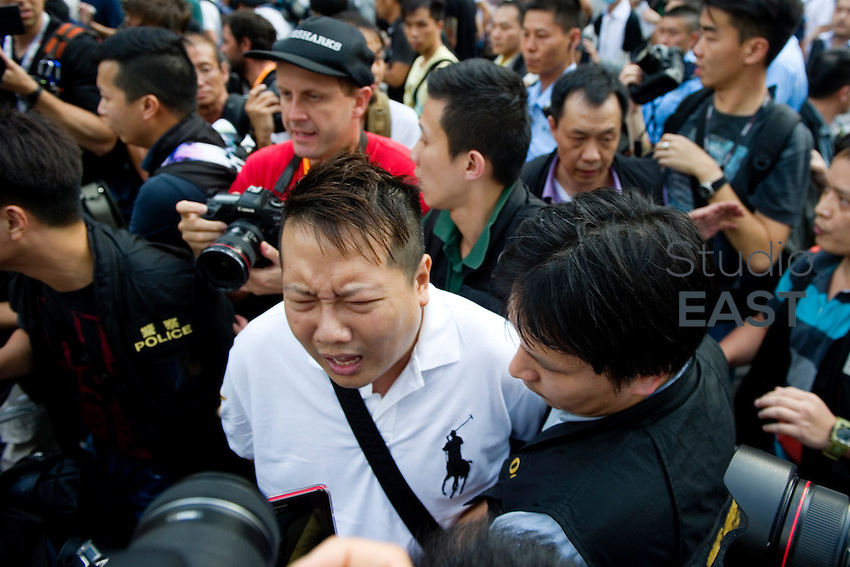 HONG KONG, HONG KONG SAR, CHINA - OCTOBER 13: Scuffles break out as police arrest an 'Occupy Central' protester (in white) in front of Pacific Place shopping mall in Queensway, Admirality, Hong Kong, China, on October 13, 2014. Hundreds of men attempted to break through barricades erected by Hong Kong pro-democracy protesters near the city's business district, as a third week of rallies tried the patience of truck and cab drivers. 'Occupy Central' protesters came back and sit on the pavement to make sure Queensway stayed theirs. The 'Umbrella revolution' or 'Occupy Central' is a civil disobedience movement that began in response to China's decision to allow only Beijing-vetted candidates to stand in the city's 2017 election for the top civil position of chief executive. Thousands of pro-democracy supporters are calling for open elections and the resignation of Hong Kong's Chief Executive Leung Chun-ying. (Photo by Lucas Schifres/Getty Images)